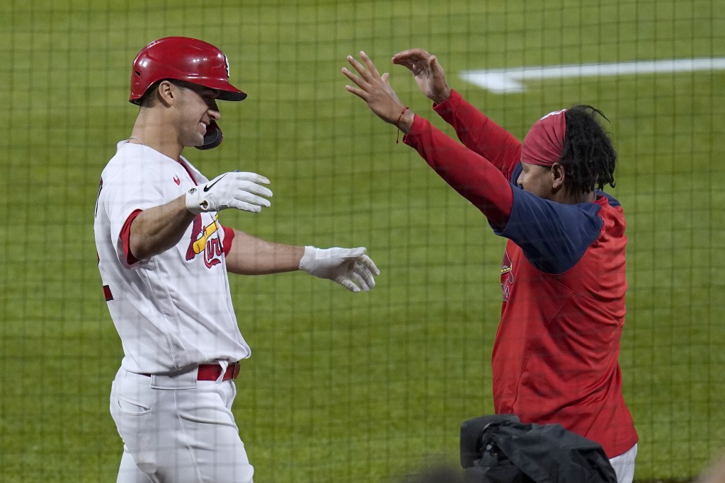 St. Louis Cardinals' Jack Flaherty, left, gets a hug from teammate Carlos Martinez after hitting a solo home run during the third inning of a baseball...