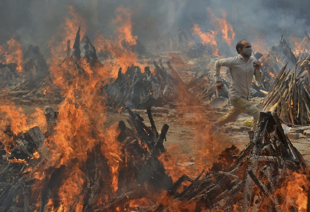 A man runs to escape heat emitting from the multiple funeral pyres of COVID-19 victims at a crematorium in the outskirts of New Delhi, India, Thursday...