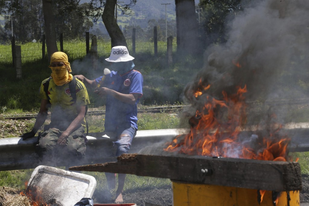 Protesters stand by a burning roadblock in Gachancipa, Colombia, Friday, May 7, 2021. Protests that began last week over a tax reform proposal continu...