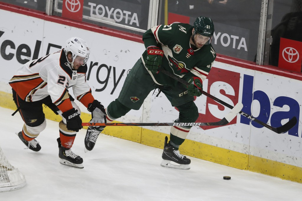 Minnesota Wild's Carson Soucy (21} goes after the puck against Anaheim Ducks' Sam Steel (23) during the first period of an NHL hockey game Friday, May...