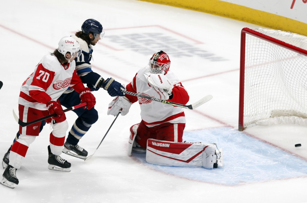 Columbus Blue Jackets forward Kevin Stenlund, center, watches a goal by teammate Gavin Bayreuther (not shown) between Detroit Red Wings defenseman Tro...