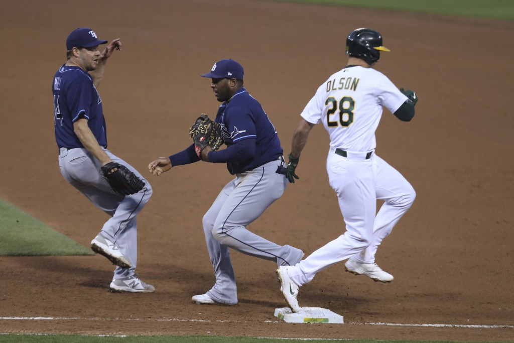 Tampa Bay Rays' Yandy Diaz, center, puts out Oakland Athletics' Matt Olson, right, as Rich Hill watches during the sixth inning of a baseball game in ...
