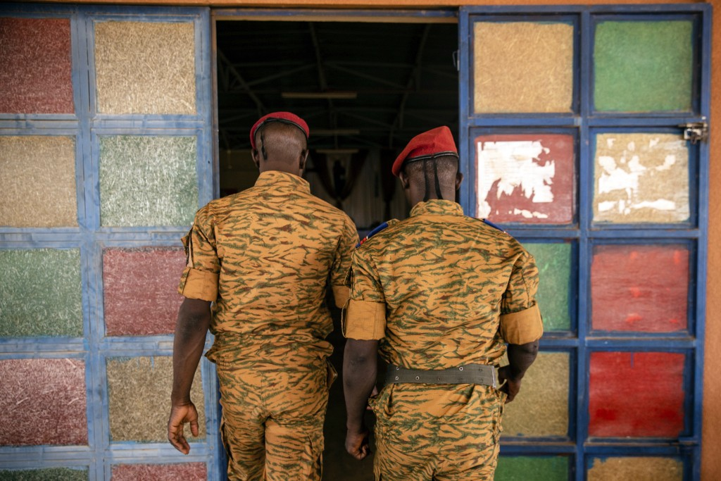 Two soldiers enter the Catholic church at the 10th RCAS army barracks in Kaya, Burkina Faso, Saturday, April 10, 2021. Once considered a beacon of pea...