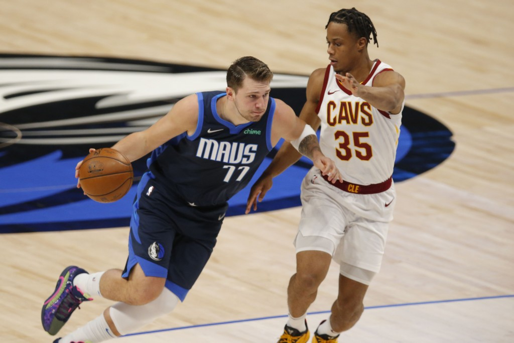 Dallas Mavericks guard Luka Doncic (77) drives against Cleveland Cavaliers forward Isaac Okoro (35) during the first half of an NBA basketball game, F...