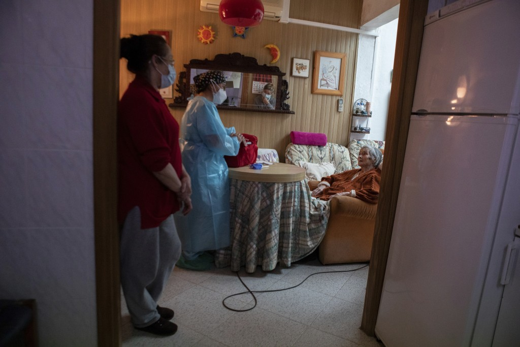 Nurse Pilar Rodríguez speaks with her patient Antonia Crespi Gomila after administering the vaccine against COVID-19 at her home in the town of Sa Pob...