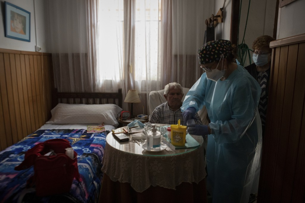 Nurse Pilar Rodríguez administers the COVID-19 vaccine to her patient Martín Gomila Serra, 82, at his home in the town of Sa Pobla on the Spanish Bale...