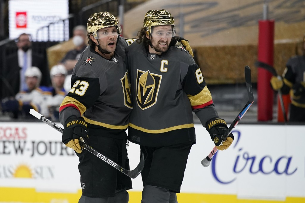 Vegas Golden Knights right wing Mark Stone, right, celebrates after defenseman Alec Martinez, left, scored a goal against St. Louis Blues during the s...