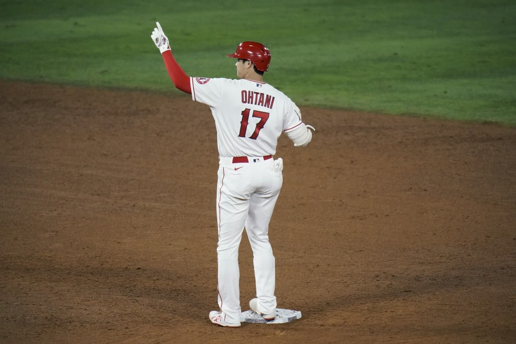 Los Angeles Angels' Shohei Ohtani, of Japan, celebrates his RBI double during the sixth inning of a baseball game against the Los Angeles Dodgers, Fri...