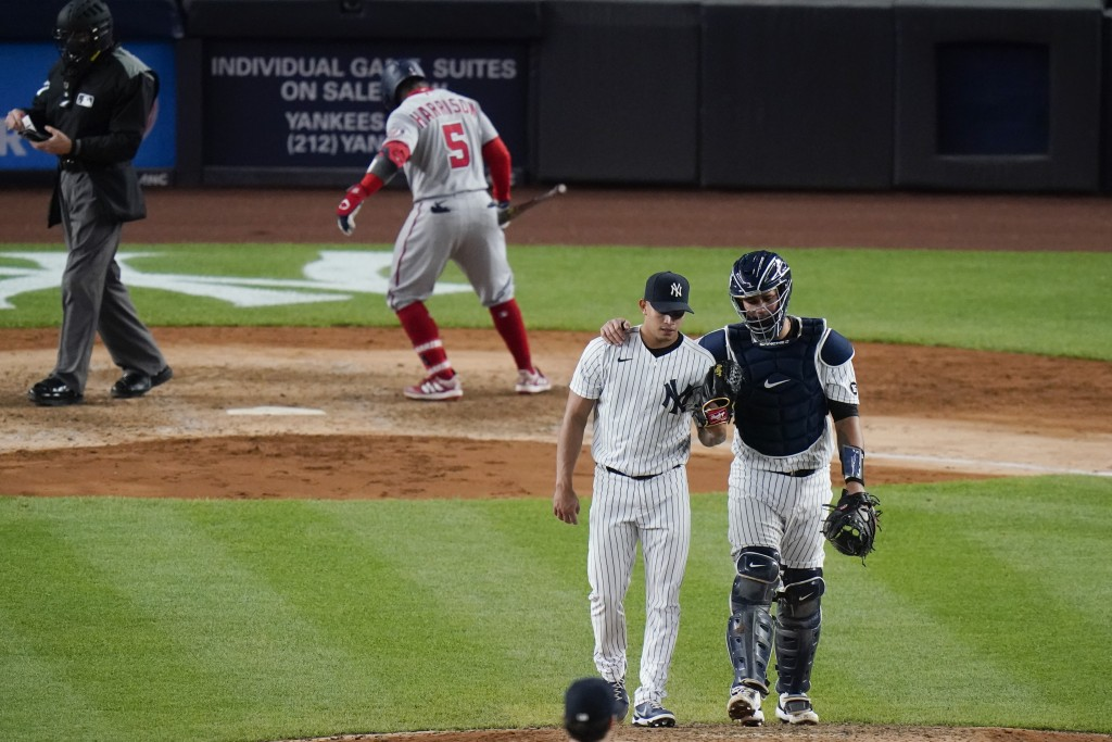 New York Yankees catcher Gary Sanchez, right, talks to Jonathan Loaisiga during the eighth inning of a baseball game as Washington Nationals' Josh Har...
