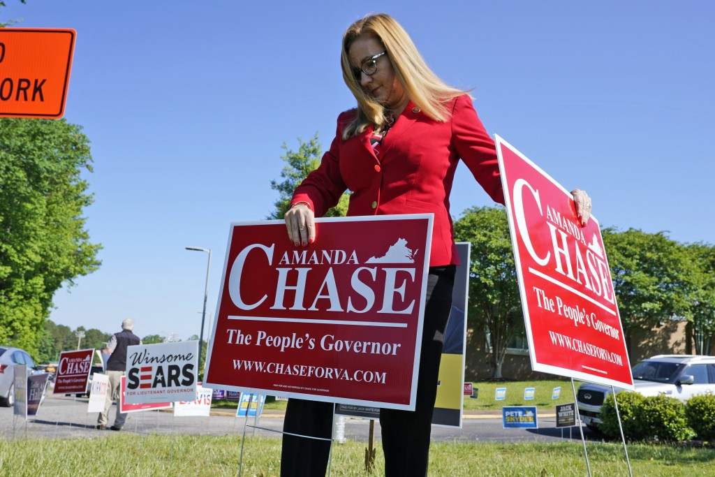 Republican gubernatorial candidate State Sen. Amanda Chase, places a yard sign during a drive through GOP Convention vote in Chesterfield, Va., Saturd...