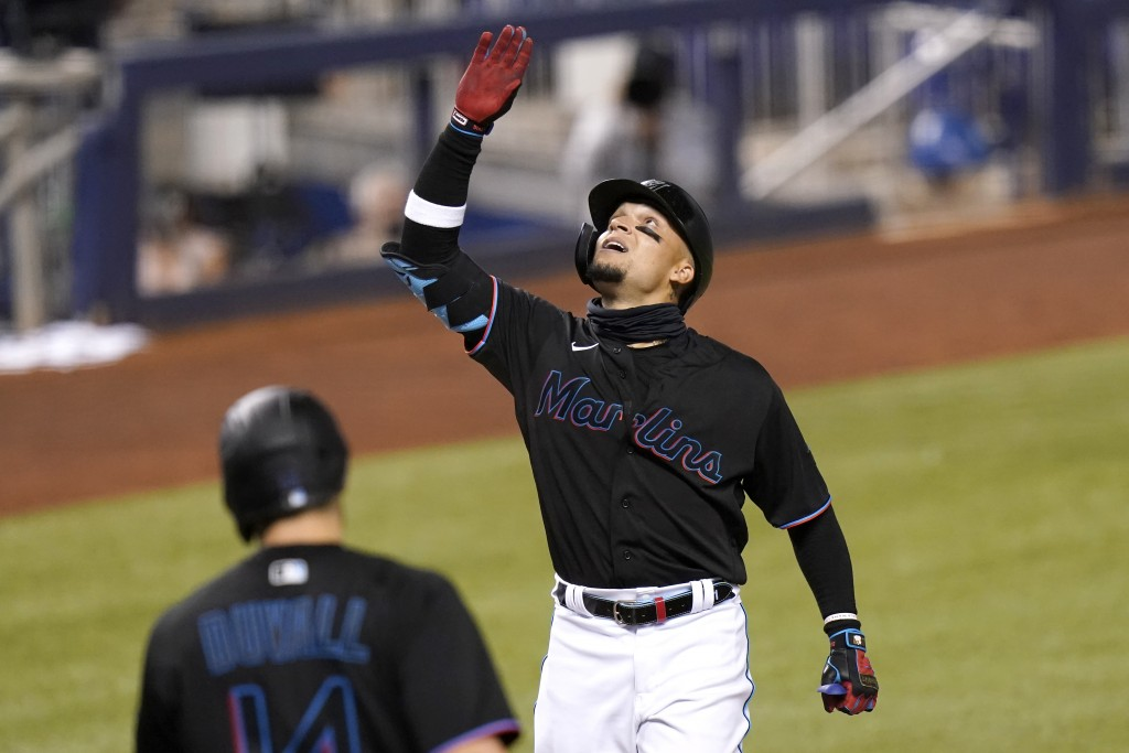Miami Marlins' Isan Diaz reacts as he crosses the plate to score after hitting a grand slam during the third inning of a baseball game against the Mia...