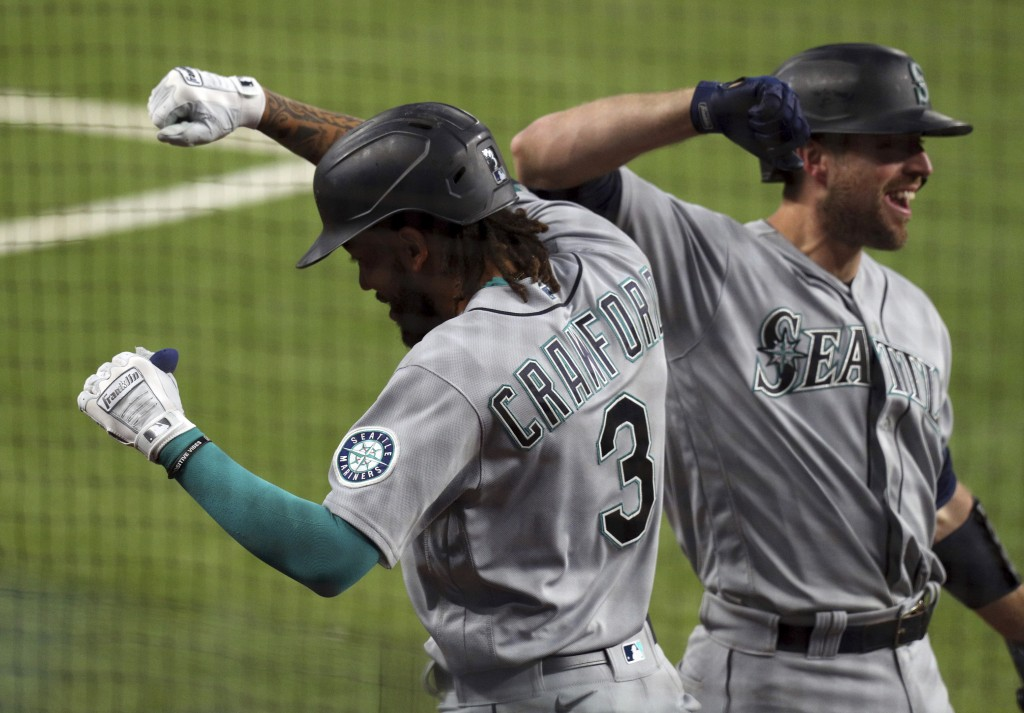 Seattle Mariners' J.P. Crawford (3) celebrates his fourth-inning, two-run home run with Tom Murphy against the Texas Rangers during a baseball game Fr...