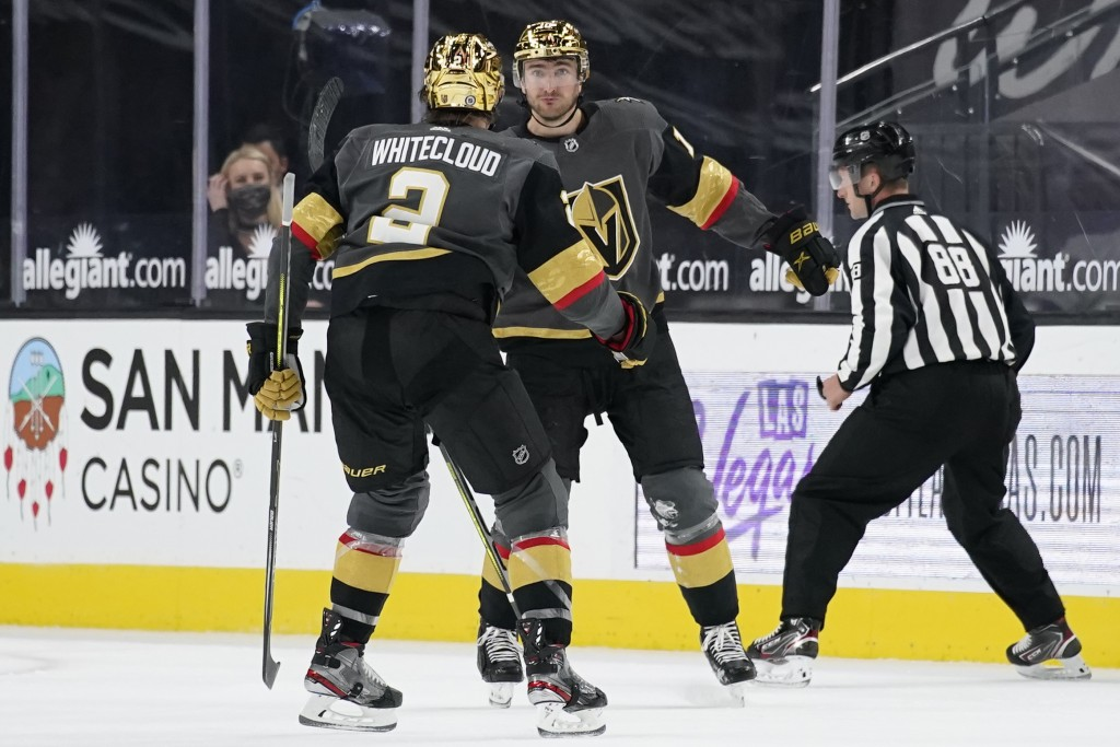 Vegas Golden Knights defenseman Zach Whitecloud (2) celebrates after center Nicolas Roy, right, scored against the St. Louis Blues during the third pe...