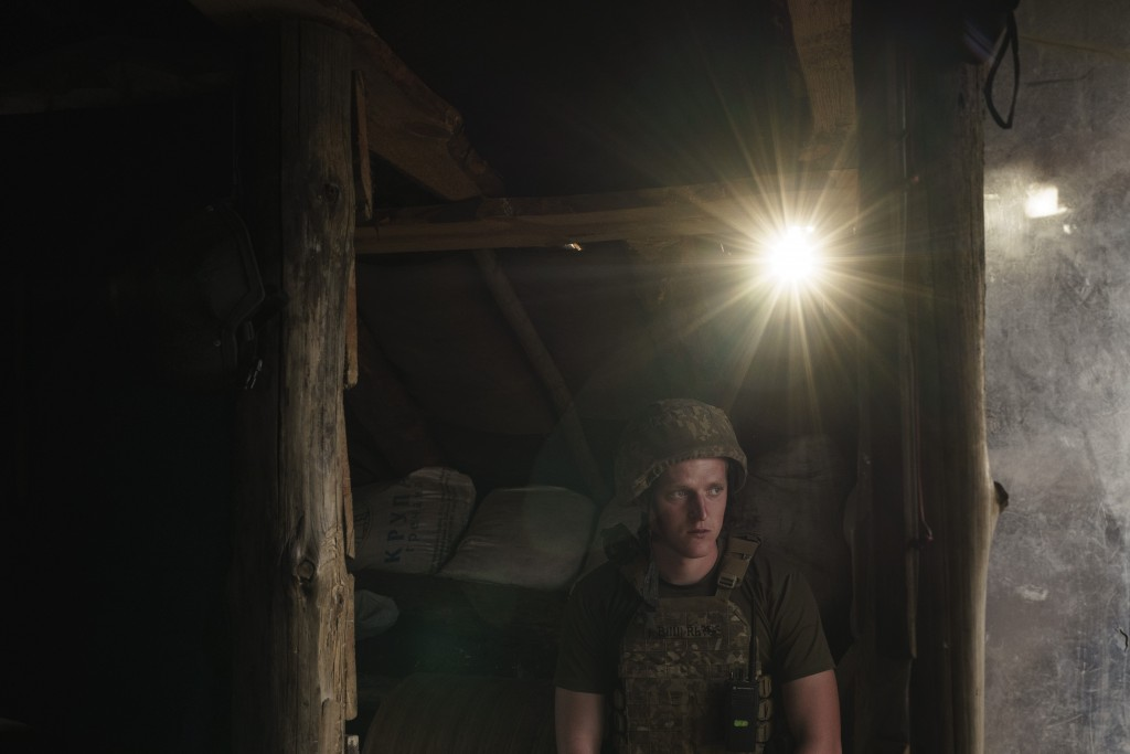 A Ukrainian soldier sits in a trench at a fighting position on the line of separation from pro-Russian rebels near Toretsk, eastern Ukraine, Thursday,...