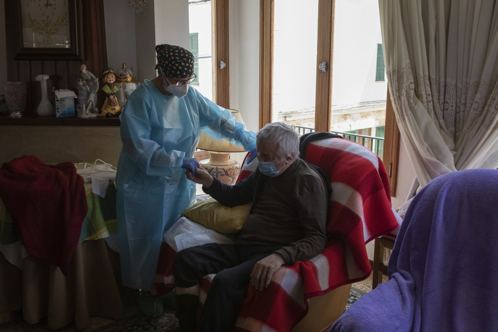 Nurse Pilar Rodríguez comforts Antonio Comas Serra, 80, after receiving the vaccine against COVID-19 at his home in the town of Sa Pobla on the Spanis...