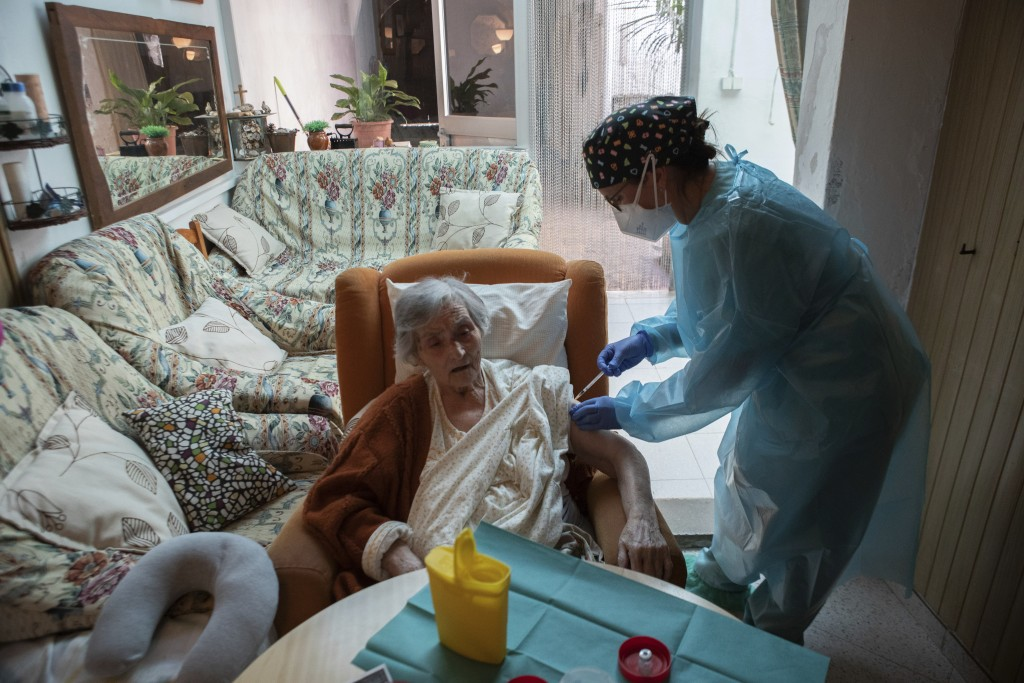 Nurse Pilar Rodríguez administers the COVID-19 vaccine to her patient Antonia Crespi Gomila, 93, at her home in the town of Sa Pobla on the Spanish Ba...