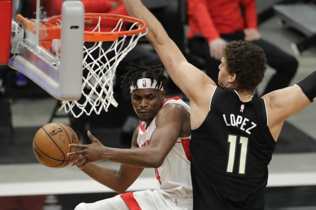 Houston Rockets' Danuel House Jr. (4) passes the ball around Milwaukee Bucks' Brook Lopez (11) during the first half of an NBA basketball game Friday,...