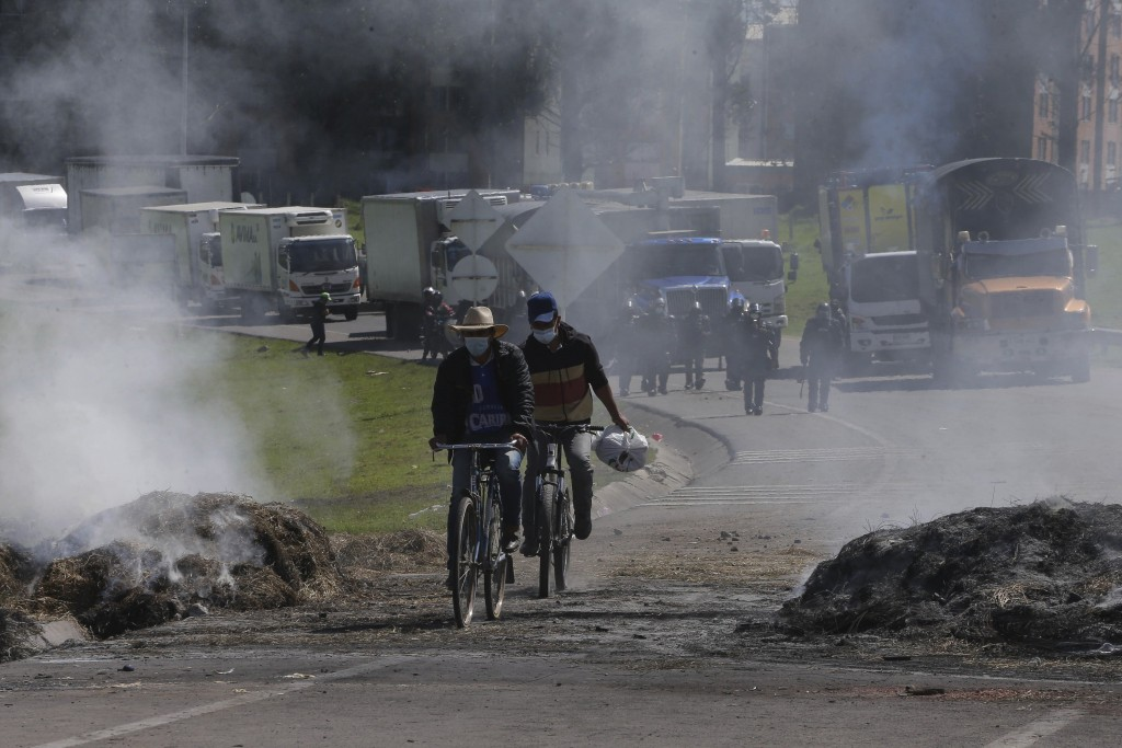 People cycle past trucks that are stuck behind a road block set up by anti-government protesters in Gachancipa, Colombia, Friday, May 7, 2021. Protest...