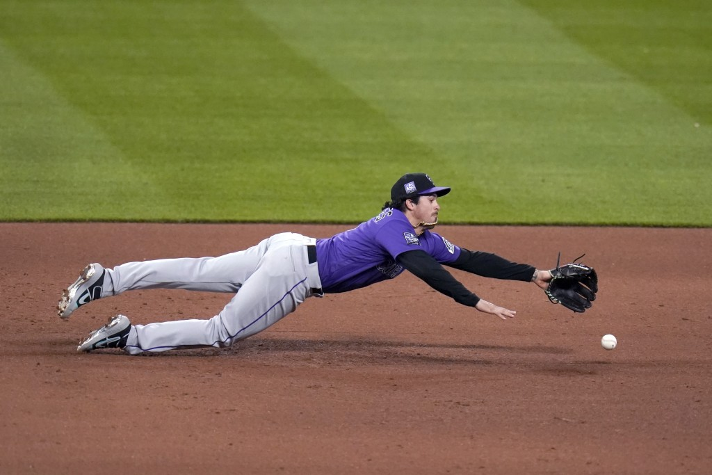 Colorado Rockies third baseman Josh Fuentes is unable to reach a single by St. Louis Cardinals' Tommy Edman during the fifth inning of a baseball game...