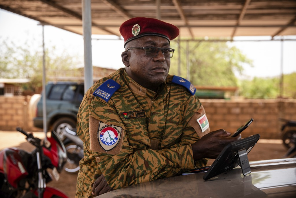 Salomon Tibiri, a pastor and military chaplain, checks his phone at the 10th RCAS barracks in Kaya, Burkina Faso, Saturday, April 10, 2021. Tibiri has...
