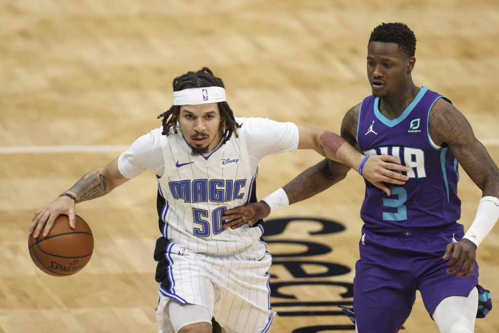 Orlando Magic guard Cole Anthony (50) brings the ball up next to Charlotte Hornets guard Terry Rozier (3) during the second half of an NBA basketball ...