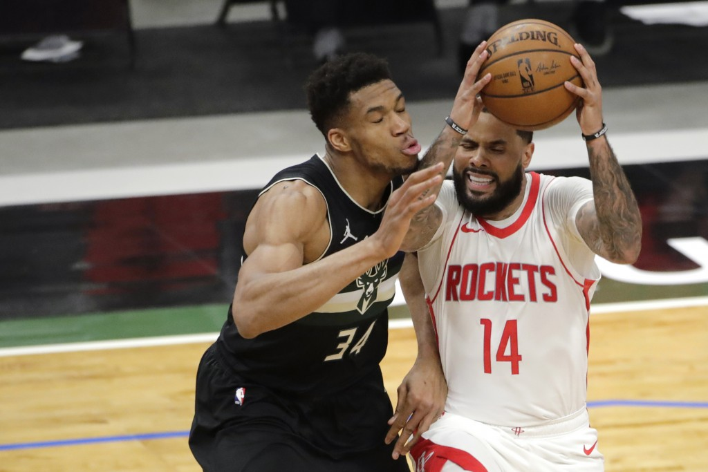 Houston Rockets' D.J. Augustin (14) drives to the basket against Milwaukee Bucks' Giannis Antetokounmpo (34) during the first half of an NBA basketbal...