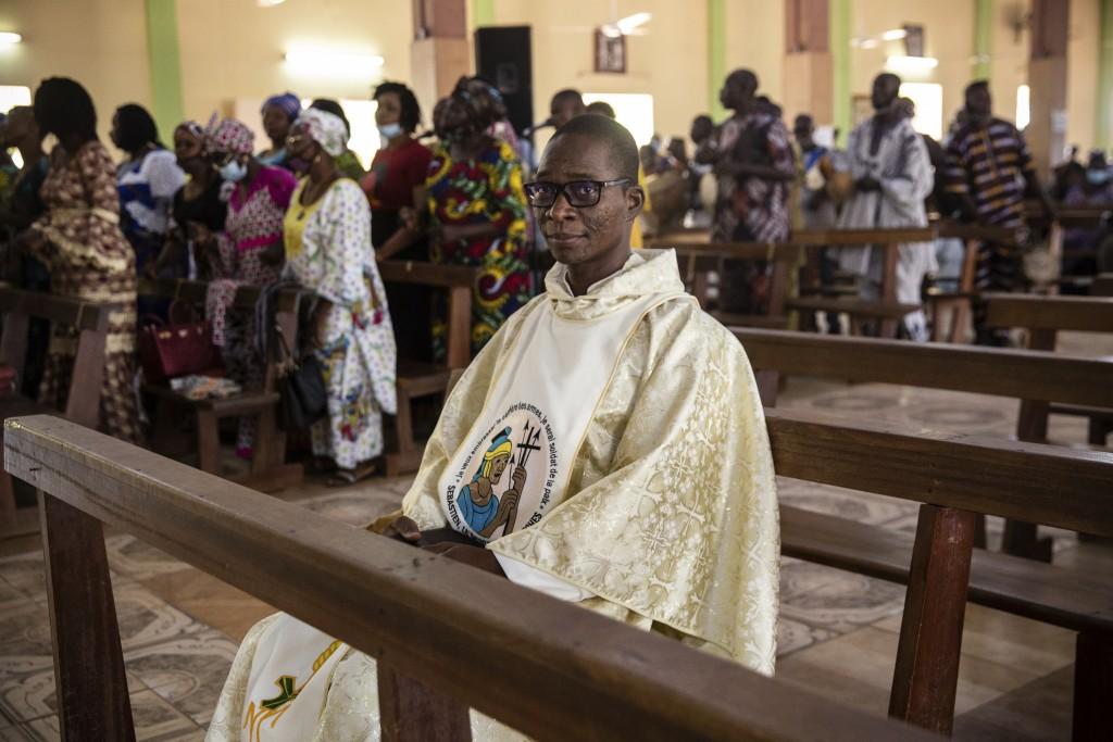 Noel Henri Zongo, a priest at the Church of the Sangoulé Lamizana military camp in Ouagadougou, Burkina Faso, poses for a portrait Sunday, April 11, 2...