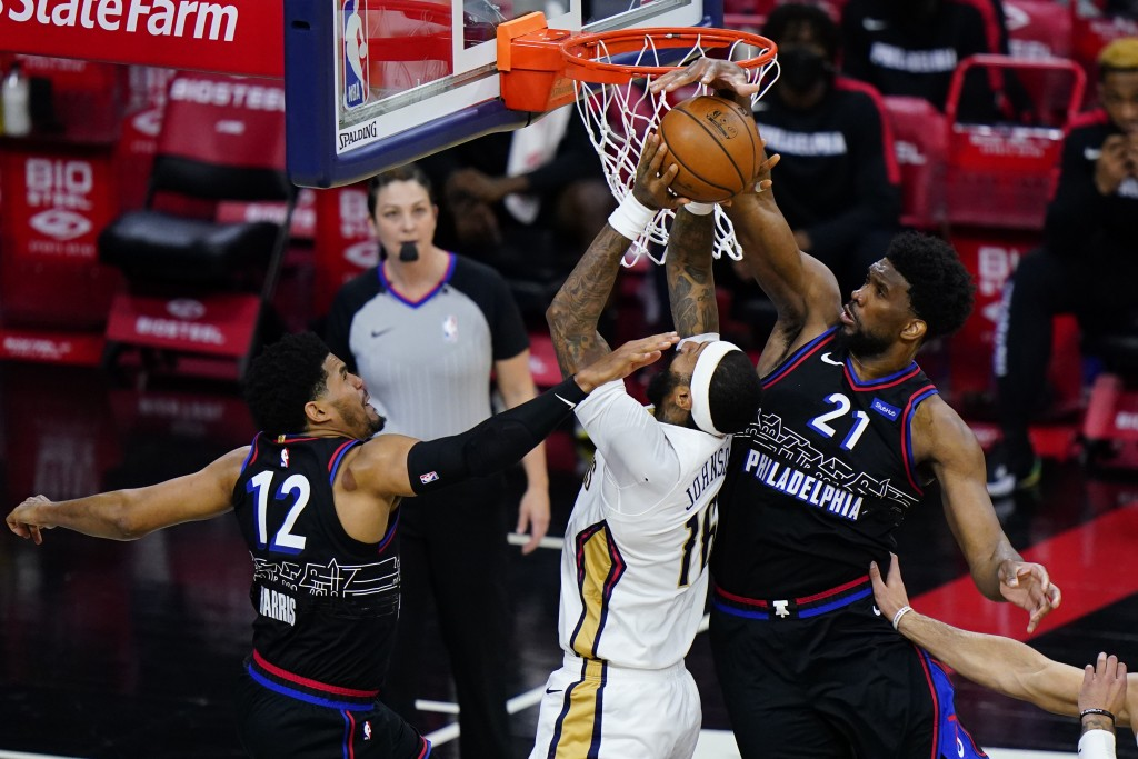 New Orleans Pelicans' James Johnson, center, cannot get a shot past Philadelphia 76ers' Joel Embiid, right, and Tobias Harris during the second half o...