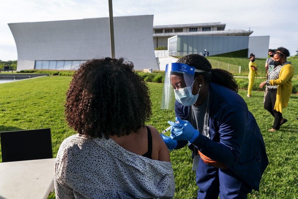 FILE - In this May 6, 2021, file photo, Kendria Brown, a nurse with DC health, vaccinates a woman with the Johnson & Johnson COVID-19 vaccine at The R...