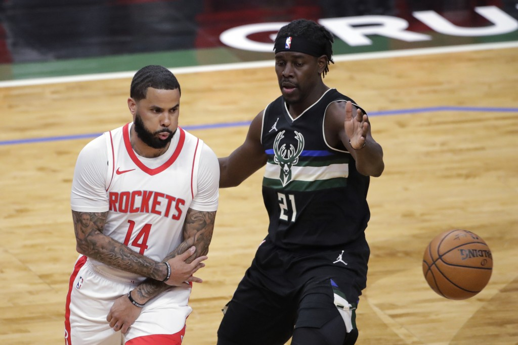 Houston Rockets' D.J. Augustin (14) passes the ball around Milwaukee Bucks' Jrue Holiday (21) during the first half of an NBA basketball game Friday, ...