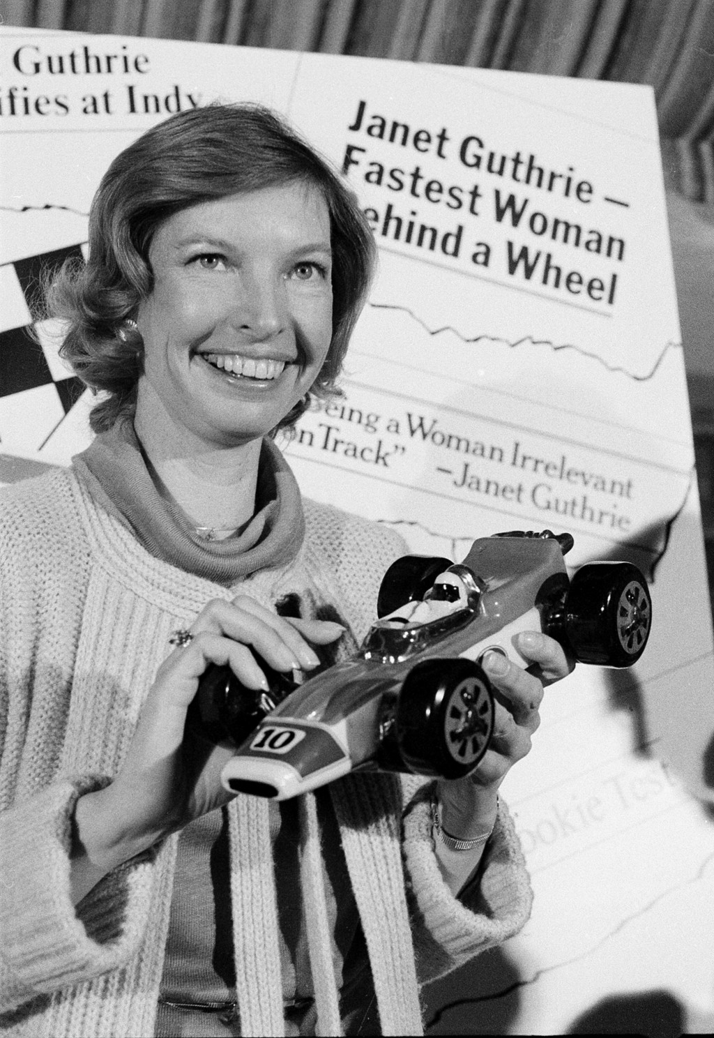 FILE - Janet Guthrie poses with a toy race car at a news conference in New York, in this April 6, 1978, file photo. Janet Guthrie is still astonished ...