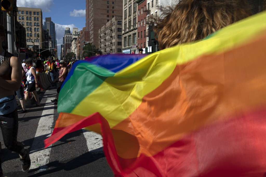 FILE - In this June 30, 2019, file photo parade-goers carrying rainbow flags walk down a street during the LBGTQ Pride march in New York, to celebrate...