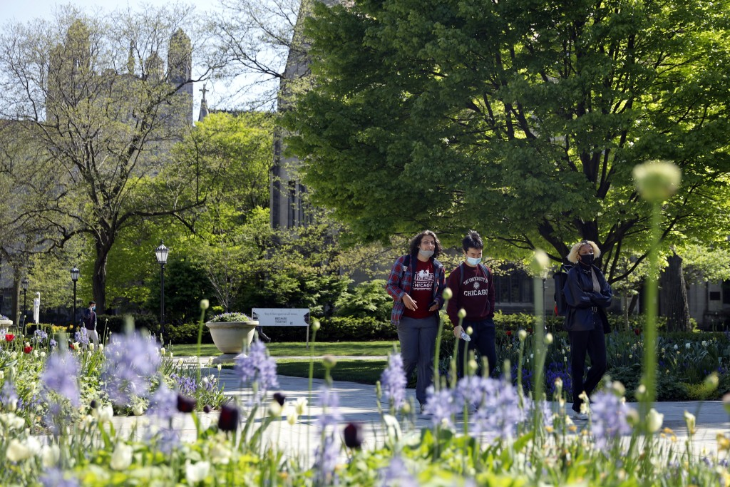 Students wearing masks make their way through the University of Chicago campus, Thursday, May 6, 2021, in Chicago. Even as restrictions relax across m...