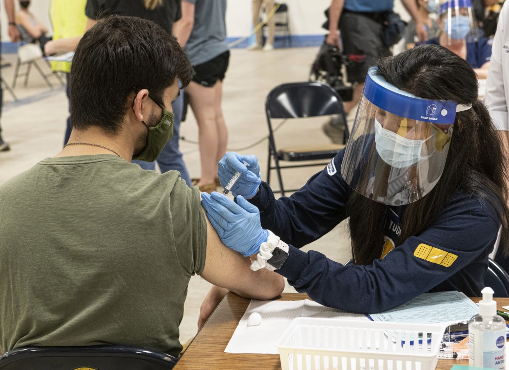 FILE - In this April 8, 2021, file photo, Kent State University student Jarrett Woo gets his Johnson & Johnson COVID-19 vaccination from Kent State nu...