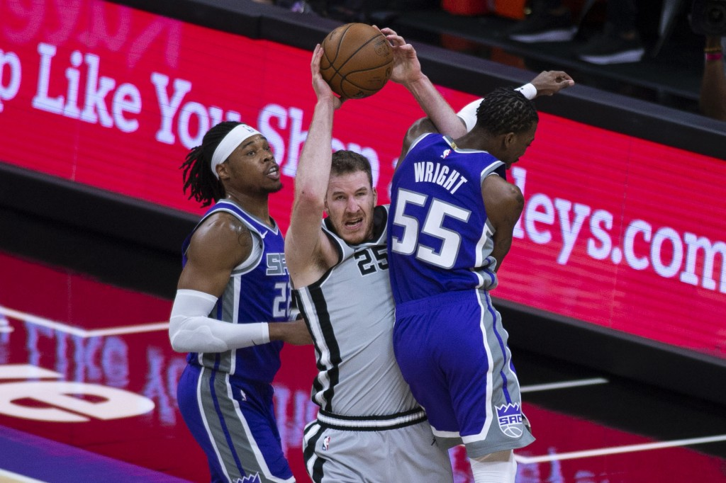 San Antonio Spurs center Jakob Poeltl (25) is fouled by Sacramento Kings guard Delon Wright (55) while Kings center Richaun Holmes (22) defends during...