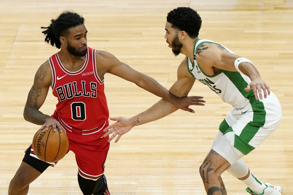 Chicago Bulls guard Coby White, left, drives against Boston Celtics forward Jayson Tatum during the second half of an NBA basketball game in Chicago, ...