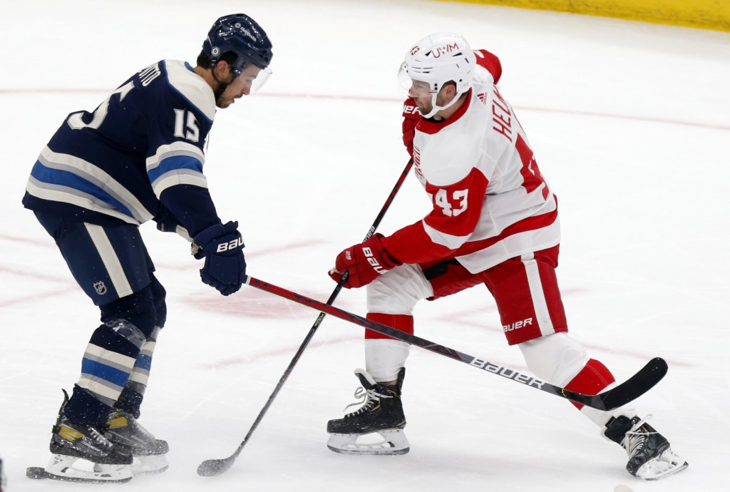 Detroit Red Wings forward Darren Helm, right, works against Columbus Blue Jackets defenseman Michael Del Zotto during the first period of an NHL hocke...