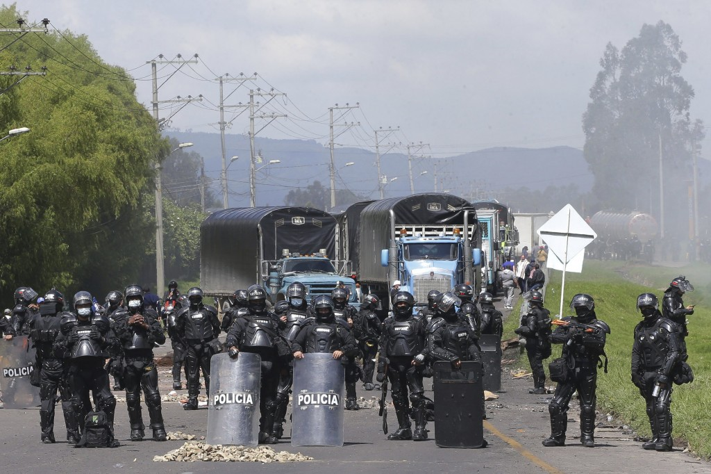 Police face anti-government protesters who are blocking a highway in Gachancipa, Colombia, Friday, May 7, 2021. Protests that began last week over a t...