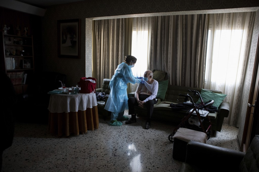 Nurse Pilar Rodríguez administers the COVID-19 vaccine to Rafael Capo Frau, 92, at his home in the town of Sa Pobla on the Spanish Balearic Island of ...