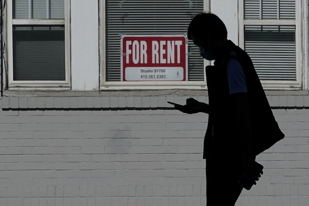 FILE - In this Oct. 20, 2020 file photo, a man walks in front of a For Rent sign in a window of a residential property in San Francisco. The Biden adm...