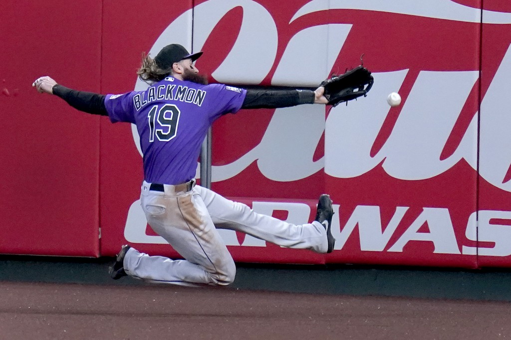 Colorado Rockies right fielder Charlie Blackmon is unable to catch a ground-rule double by St. Louis Cardinals' Nolan Arenado during the second inning...