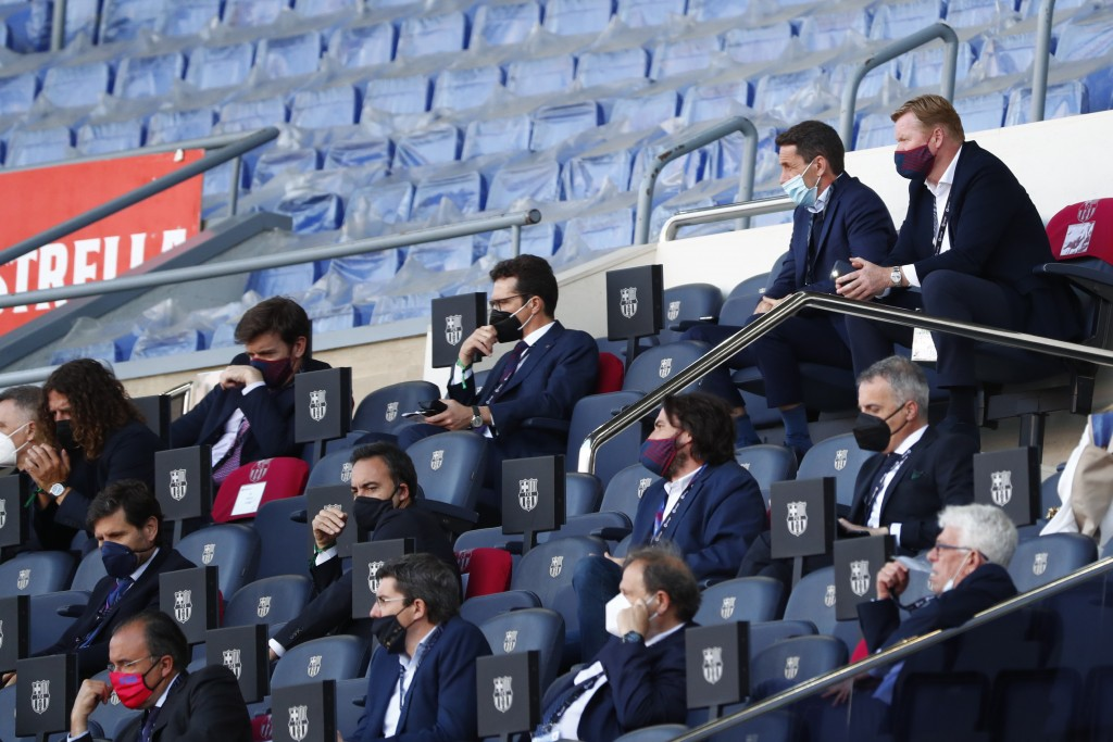 Barcelona's head coach Ronald Koeman, top right, watches from stands during the Spanish La Liga soccer match between FC Barcelona and Atletico Madrid ...