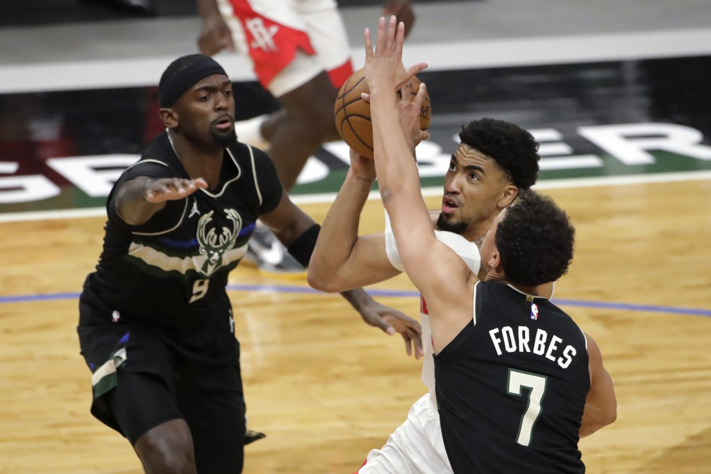 Houston Rockets' Kenyon Martin Jr. drives to the basket between Milwaukee Bucks' Bryn Forbes (7) and Bobby Portis (9) during the first half of an NBA ...