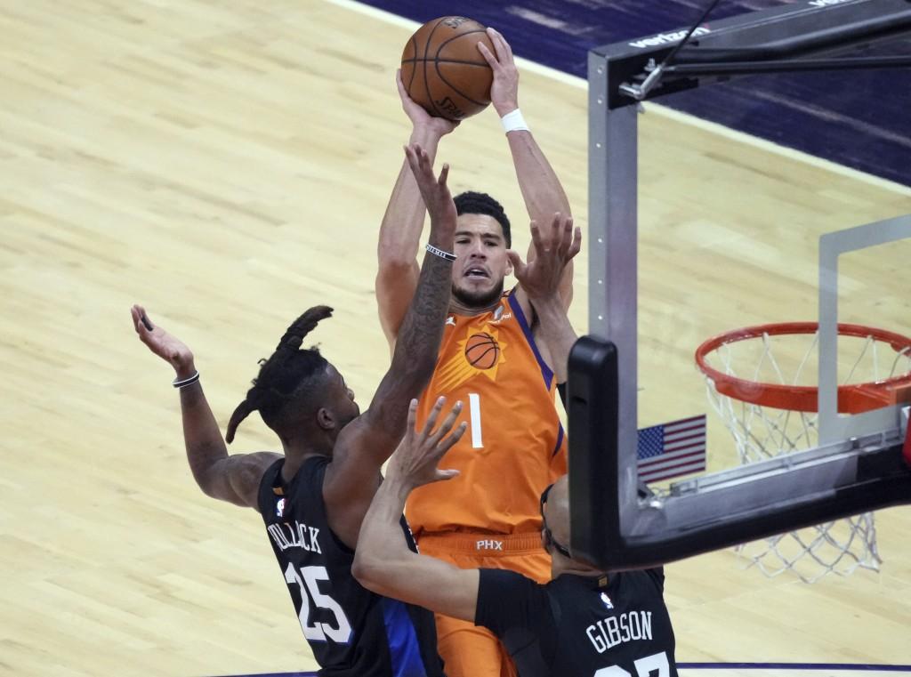 Phoenix Suns guard Devin Booker (1) shoots over New York Knicks forward Reggie Bullock (25) and center Taj Gibson during the first half of an NBA bask...