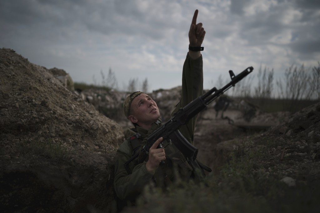 A Ukrainian soldier points at a passing helicopter as he stands in a trench on the line of separation from pro-Russian rebels near Donetsk, Ukraine, M...