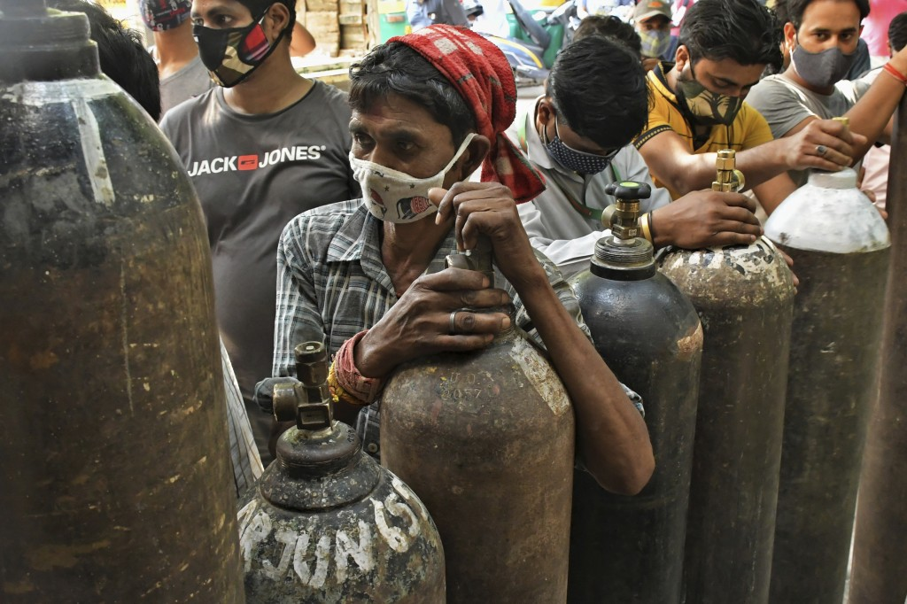 Indians wait to refill oxygen cylinders for COVID-19 patients at a gas supplier facility in New Delhi, India, Saturday, May 8, 2021. Infections have s...