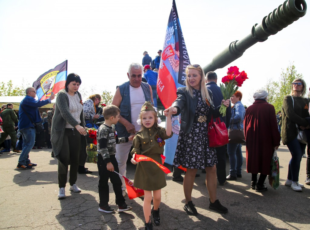 A girl wearing Soviet-era military uniform and her relative walks past a cannon during celebrations of the Victory Day at a World War II memorial in S...