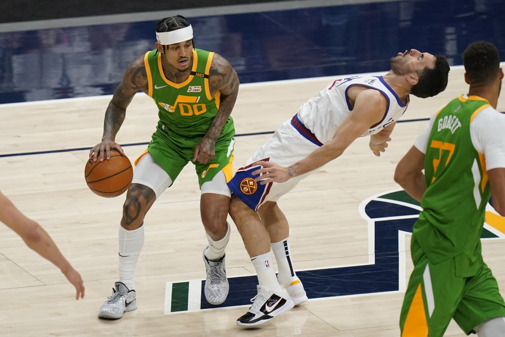 Denver Nuggets guard Facundo Campazzo, right, falls as Utah Jazz guard Jordan Clarkson (00) drives during the first half of an NBA basketball game Fri...