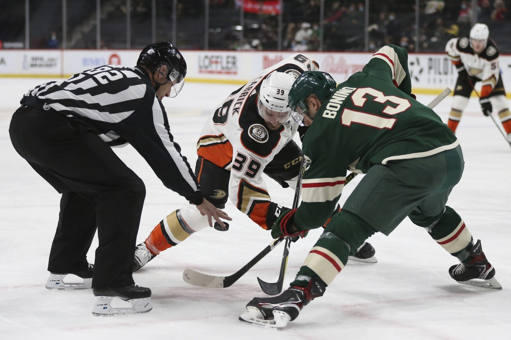 Linesman Ryan Galloway (82) drops the puck for faceoff between Anaheim Ducks' Sam Carrick (39) and Minnesota Wild's Nick Bonino (13) during the second...