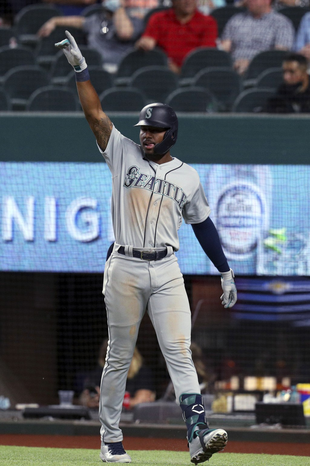 Seattle Mariners' Taylor Trammell gestures toward Mitch Haniger after scoring against the Texas Rangers during the seventh inning of a baseball game F...